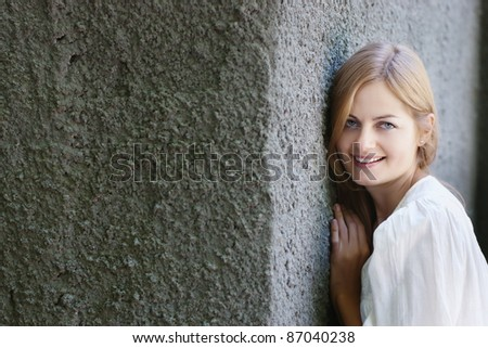 Beautiful blue-eyed smiling woman in blue against rough stone wall with selective focus and copy space