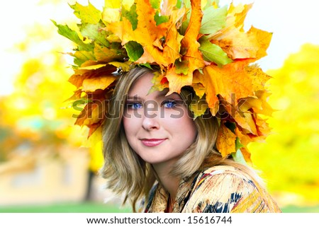 Beautiful blue-eyed woman with diadem made from yellow maple leaves