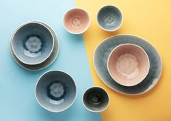 Beautiful blue, grey, beige dinnerware, plates bowls on lilac table, top view, toned, selective focus