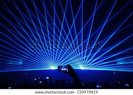 beautiful blue laser beam in concert with crowded people holding #720979819