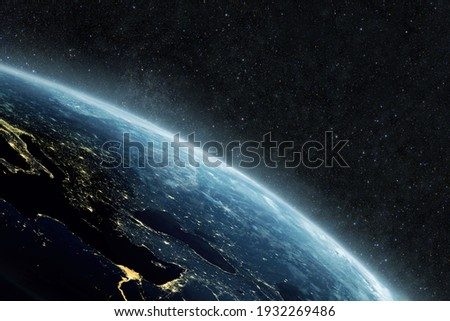 Beautiful blue planet earth with yellow city lights on the starry background in outer space