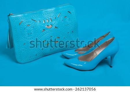 Beautiful blue shoes and handbag on blue background