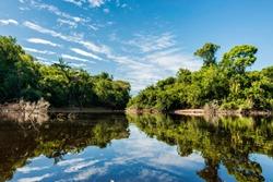 Beautiful blue sky reflecting in the Amazonia Basin river. Corocoro river goes along Yutaje Community whicth mean in the native language:  River Foam (Espuma del Rio)