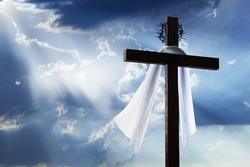 Beautiful blue sky with clouds and sunbeams shining on a cross for Easter morning. The cross includes burial cloth and crown of thorns.