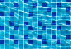 Beautiful blue square tiles under swimming pool with shinny ripple on transparent water surface, symmetry, texture, pattern background.