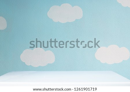 beautiful blue wall with clouds and empty white tabletop in cute nursery
