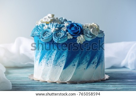 Beautiful blue wedding cake decorated with white flowers of cream with a place for a label. The concept of Holiday desserts for a birthday