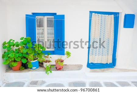 Beautiful blue wooden box with shutters and curtains in the old house on the streets of the Greek islands. Mykonos. Greece.