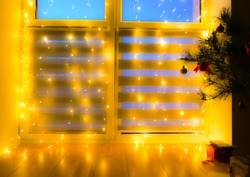 Beautiful blurred flickering yellow light. Home decoration with garlands on the window, night Bokeh lighting. Festive background.