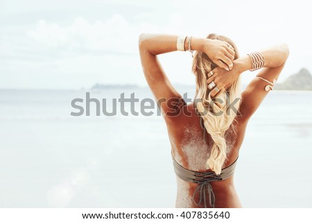 Beautiful bohemian styled and tanned girl at the beach in sunlight