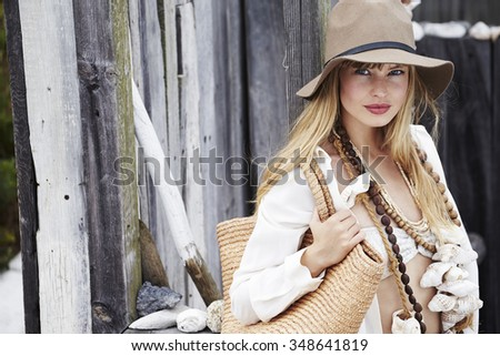 Beautiful boho fashion model with bag and necklace