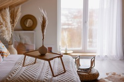 beautiful boho interior details. Pampas grass in a vase. Hygge mood. Cozy morning in the fall. Bedroom in a country house. The bed is covered with a blanket. coffee table. Relax environment