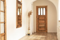 Beautiful boho interior of hallway at cozy apartment. Minimalistic Mediterranean style and design accessories. Stylish home decor.