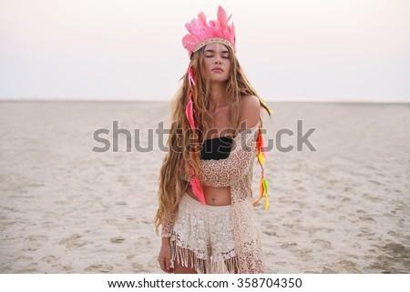 Beautiful boho styled girl with long hair on the sunset beach