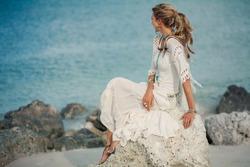 beautiful boho woman sitting on stone at sea shore