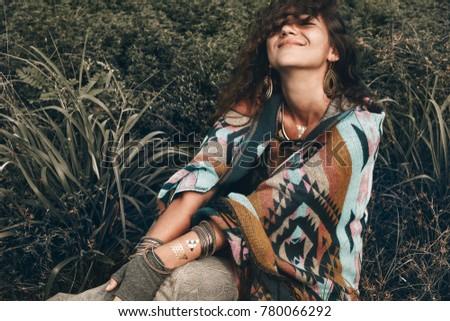 Beautiful boho woman wearing poncho on green field - Shutterstock ID 780066292