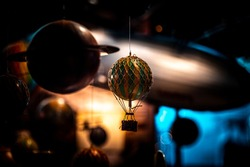 Beautiful bokeh of a small hot air balloon toy hanging with planets and airships in the background. Concept of nostalgic memories of astonishment for science.