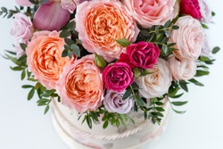 beautiful bouquet in a box on a white table, top view, close-up with blurred background, peony rose, pink rose, purple rose, greens