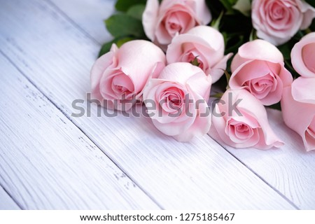 Beautiful bouquet of blooming long stem pink roses catching soft morning sunlight on cream-colored wood background. Closeup, selective focus. Love, Romance, Valentine's Day,