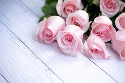 Beautiful bouquet of blooming long stem soft pink roses catching morning sunlight on cream-colored wood background. Closeup, selective focus.  Love, Valentine's Day, Mother Day.