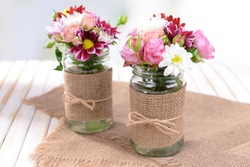 Beautiful bouquet of bright flowers in jars on table on light background