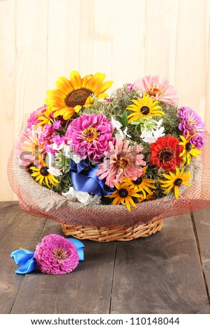 Beautiful bouquet of bright flowers in sacking on wooden background - stock photo