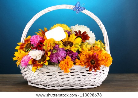Beautiful bouquet of bright flowers in white basket on wooden table on blue background