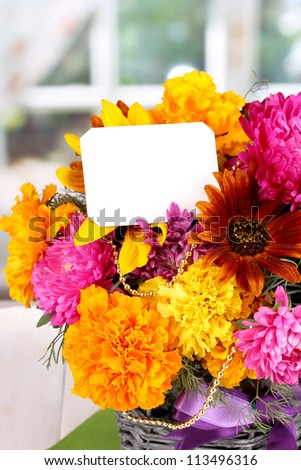 Beautiful bouquet of bright flowers with paper note on wooden table on window background