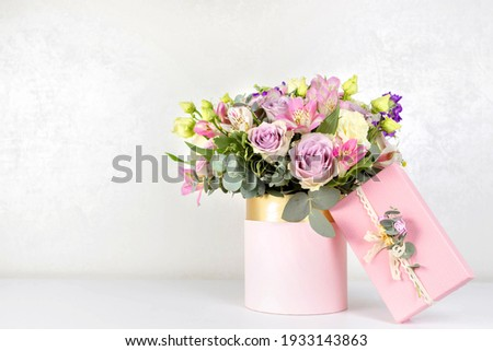 Beautiful bouquet of flowers in round box and pink gift box on a white table. Gift for holiday, birthday, Wedding, Mother's Day, Valentine's day, Women's Day. Floral arrangement in a hat box. Сток-фото ©
