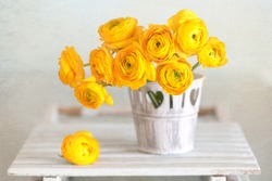 Beautiful bouquet of flowers.Yellow ranunculus flowers close-up in a vase on the table.