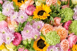 beautiful bouquet of mixed flowers in a vase on wooden table. the work of the florist at a flower shop. a bright mix of sunflowers, chrysanthemums and roses. background on full screen