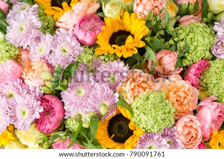 beautiful bouquet of mixed flowers in a vase on wooden table. the work of the florist at a flower shop. a bright mix of sunflowers, chrysanthemums and roses. background on full screen #790091761