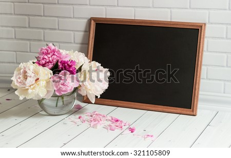 Beautiful bouquet of pink and white peonies in the glass vase with petals and black chalkboard with empty place for your text on the light grey brick and wood background.