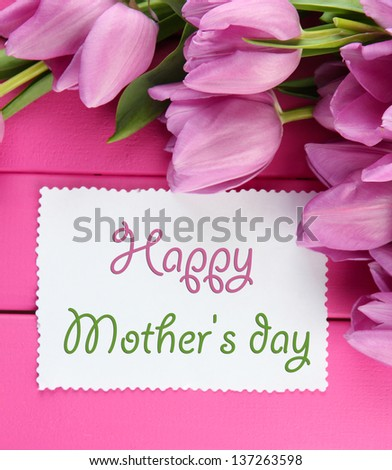 Beautiful bouquet of purple tulips and blank card on pink wooden background