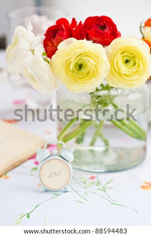 beautiful bouquet of ranunculus into a vase and alarm clock