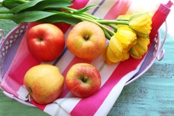 Beautiful bouquet of tulips with fruits on napkin close up