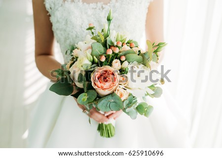 Beautiful bouquet. The bride is holding a bouquet in her hands. Flowers of the bride. The bride is waiting for the groom in the white room. Stock photo ©