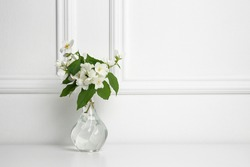 Beautiful bouquet with fresh jasmine flowers in vase on white table indoors, space for text