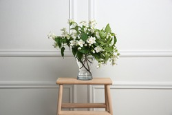 Beautiful bouquet with fresh jasmine flowers in vase on wooden table indoors