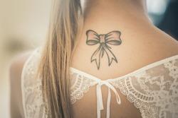 beautiful bow tatoo on bridal neck. (vintage effect)
