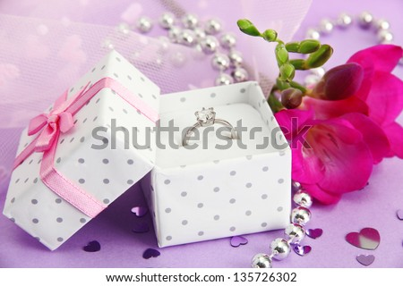 Beautiful box with wedding ring and flower on purple background