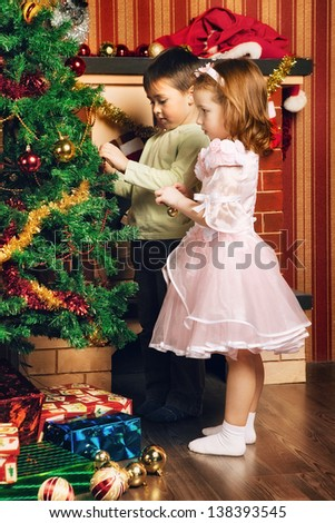 beautiful boy and girl decorate christmas tree