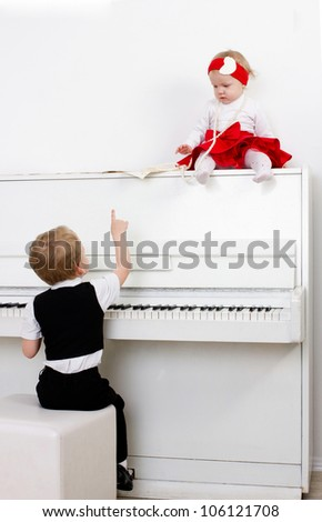 beautiful boy and girl near white piano