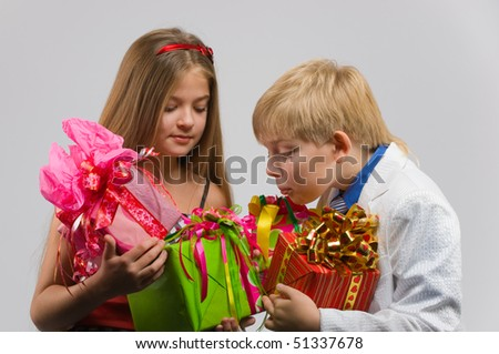 beautiful boy and girl standing side by side with gifts in their hands