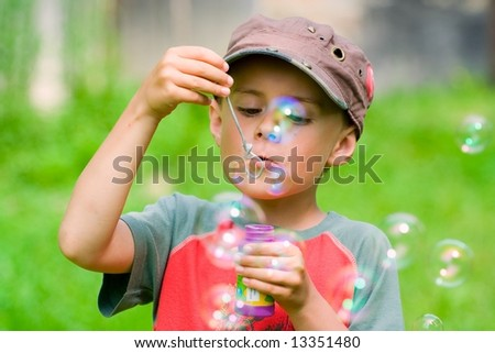 Beautiful boy blowing soap bubbles outdoors