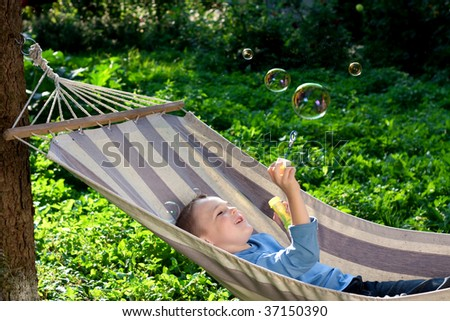 Beautiful boy blowing soap bubbles outdoors, summer