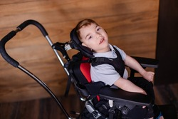 beautiful boy child in a special wheelchair. Toddler with cerebral palsy. Rehabilitation process at home indoor. Lifestyle moments.