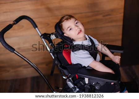 beautiful boy child in a special wheelchair. Toddler with cerebral palsy. Rehabilitation process at home indoor. Lifestyle moments.  Stock photo ©