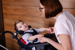 beautiful boy child in a special wheelchair. Toddler with cerebral palsy with his mother. Rehabilitation with a teacher is a process. Lifestyle moments. Rehabilitation therapist lesson therapy