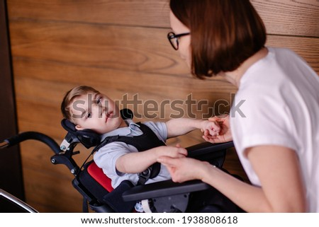 beautiful boy child in a special wheelchair. Toddler with cerebral palsy with his mother. Rehabilitation with a teacher is a process. Lifestyle moments. Rehabilitation therapist lesson therapy Stock photo ©